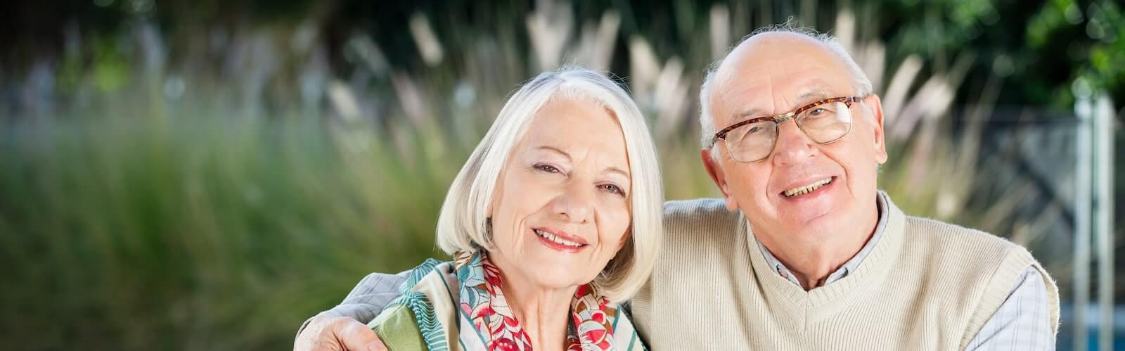 senior couple smiling sitting outside