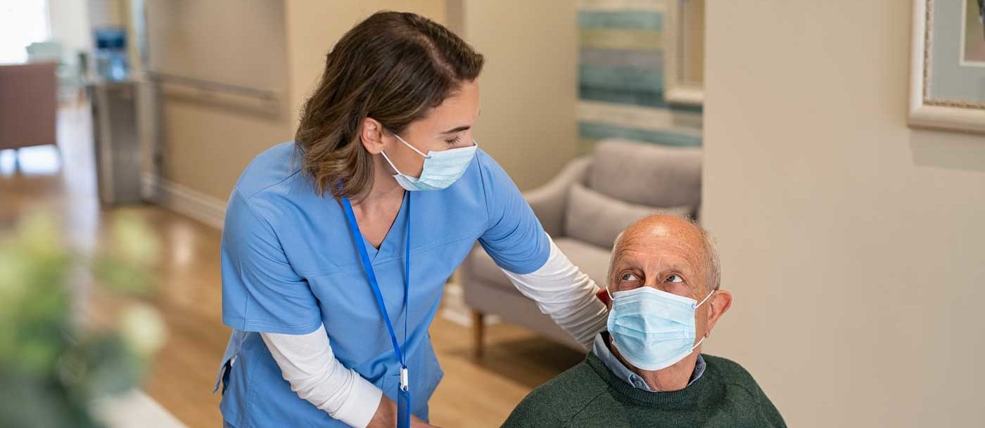 senior and healthcare worker with face masks on walking through a senior living community