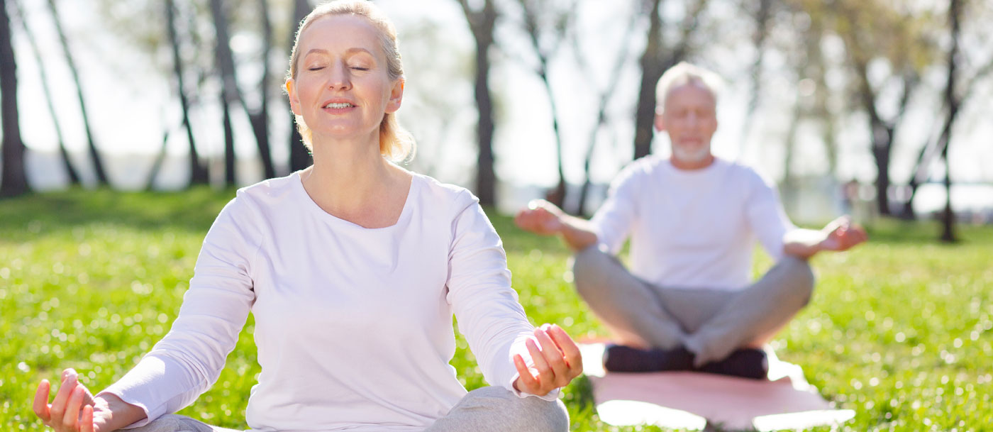 seniors practicing yoga outdoors at a retirement community